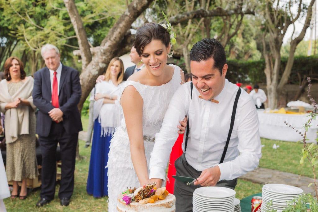 pareja de novios partiendo su pastel el dia de su boda.