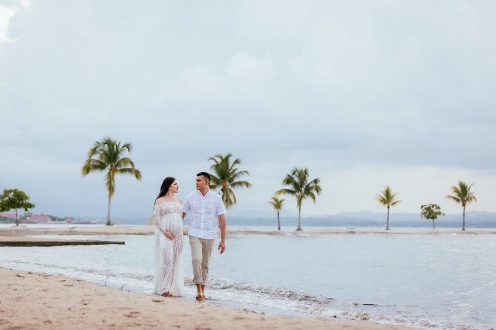 Pareja caminando sobre la playa de amatique bay durante sus fotos de embarazo.