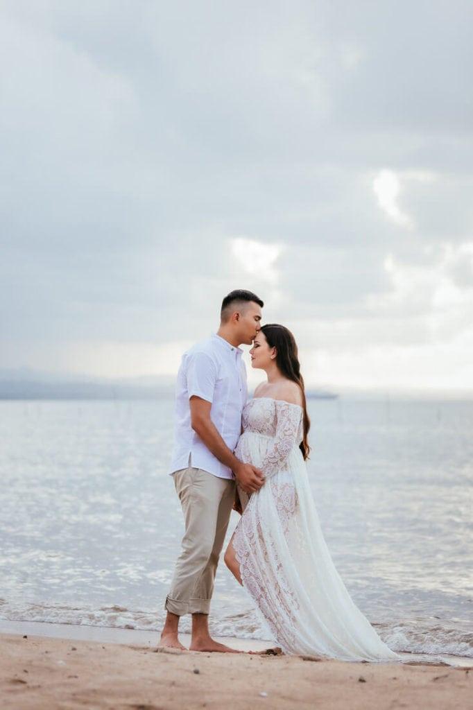 Pareja en sus fotos de embarazo en la playa de Amatique bay.